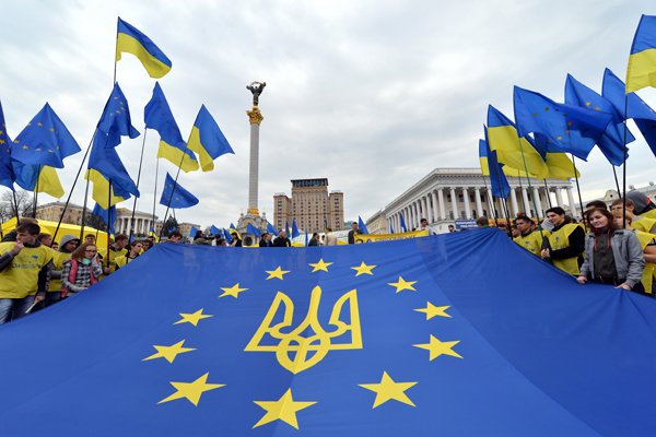 "UKRAINE, Kiev : Activists of Ukrainian movement ""For European Future"" hold EU flag with the Ukraine national emblem during their rally at Independence Square in Kiev on October 30, 2013. They have launched a campaign for a referendum in support of the European choice of Ukraine and against the country's joining to the Customs Union with Russia. AFP PHOTO/ SERGEI SUPINSKY"