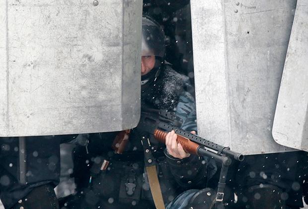 Боец «Беркута» с заряженным резиновыми пулями ружьем