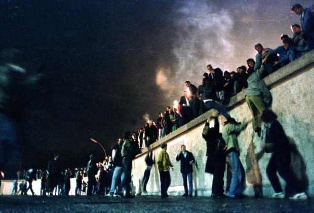 Восточные немцы перебираются через Берлинскую стену у Бранденбургских ворот после открытия границы с ФРГ. 10 ноября 1989 года