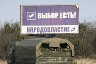 "Soldiers, believed to be Russian, look out from the back of a military truck as they drive near a sign near the Crimean port city of Sevastopol March 10, 2014. The sign reads ""there is a choice"" (top) and ""people's power"". REUTERS/Baz Ratner (UKRAINE - Tags: MILITARY POLITICS)"