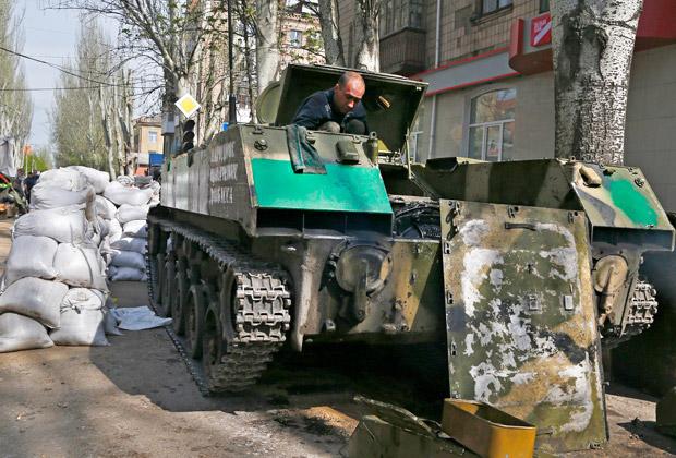 Боец ополчения ремонтирует бронетранспортер на улице Славянска