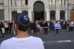 A man wearing a skullcap looks on as people take part in a demonstration called by the Representative Council of Jewish Institutions in France (CRIF) on July 31, 2014 in front of Lyon's synagogue, as France is considering disbanding a radical Jewish group, the Jewish Defence League (LDJ), whose members clashed with pro-Palestinian activists during rallies over Israel's offensive in Gaza. The rally is in response to weeks of pro-Palestinian protests marred by clashes, arrests and allegations of anti-Semitism in which synagogues were targeted and Israeli flags burnt