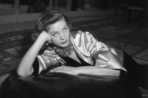 1955: Portrait of American actor Lauren Bacall wearing a coral necklace and earrings and a gold satin jacket over a black velvet body suit, seated on an oriental carpet and leaning on an ottoman.