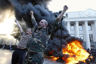 "Protesters react as tyres burn outside the Ukrainian Parliament on September 16, 2014. Clashes with police erupted during rallies organized by civic activists in central Kiev to demand Ukrainian lawmakers to adopt a ""lustration"" law that stipulates purge of governmental officials accused of corruption or affiliated with former KGB."