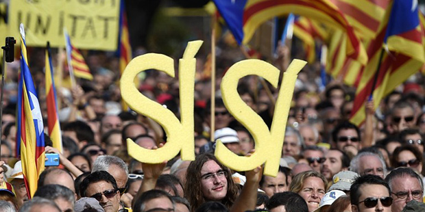 "Pro-independence Catalans, members of Omnium Cultural and National Assembly of Catalonia -ACN- demonstrate in support of the independence referendum planned for November 9 at Catalunya square in Barcelona, on October 19, 2014. Opposition parties in Catalonia on October 15 demanded a snap regional election after pressure from Madrid forced leaders to water down plans for a vote on independence from Spain. Letters read ""Yes-Yes."""