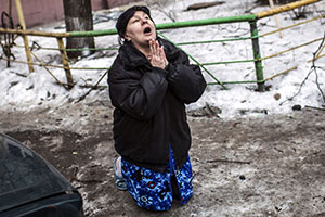 """A Ukrainian woman begs Ukrainian President Petro Poroshenko to stop the bombing in Donetsk after shell hit the residential area where she lives, killing two civilians in Donetsk's Kyibishevsky district, on January 29, 2015. Ukrainian President Petro Poroshenko on January 29 called for urgent truce talks with pro-Russian rebels to end a bloody surge in fighting. Poroshenko said the new meeting in the Belarussian capital should lead to """"an immediate ceasefire and the withdrawal of heavy weapons from the line of contact.""""  AFP PHOTO / MANU BRABO"""