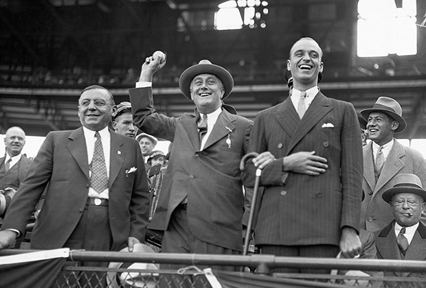 Губернатор Нью-Йорка и кандидат в президенты Франклин Рузвельт вбрасывает мяч в бейсбольном матче между Чикаго Кабс и Нью-Йорк Янкиз. Справа его сын Джеймс, слева мэр Чикаго Антон Чермак, 1932 год