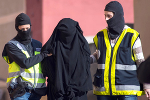 Masked Spanish police officers lead a detained woman in Melilla, December 16, 2014. Spanish and Moroccan police have arrested seven people in a ongoing joint swoop on suspected efforts to recruit women to go to Syria and Iraq to support Islamic State insurgents, the Spanish Interior Ministry said on Tuesday.