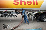 Travis Simmons, a driver for Yo-Mac Transport, stores a filling hose after delivering 7,500 gallons of unleaded gasoline to a Shell station in Peoria, Illinois, U.S., on Friday, Sept. 12, 2014. Regular gasoline at the pump, averaged nationwide, fell to $3.395 a gallon Sept. 13, the least since Feb. 21, according to Heathrow, Florida-based AAA, the largest U.S. motoring group. Photographer: Daniel Acker/Bloomberg via Getty Images