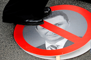 A protester steps on a sign with a portrait of Macedonian Prime Minister Nikola Gruevski during an anti-government demonstration in Skopje, Macedonia, May 17, 2015.