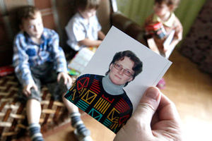 Anatoly Gorlov, husband of Russian activist Svetlana Davydova, holds up a photo of her, as their children are seen in the background, at their home in Vyazma, January 30, 2015.