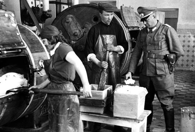 Немецкий офицер проверяет качество масла на украинской молочной ферме, 1942 год