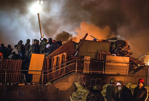 Евромайдан. Сторонники оппозиции у горящей баррикады на площади Независимости, где начались столкновения митингующих и сотрудников милиции. 2014 год