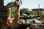 A Russia-backed rebel loads shells in a tank at Donetsk airport, eastern Ukraine, Friday, June 12, 2015. Heavy fighting continues at the frontline at the airport of Donetsk. (AP Photo/Mstyslav Chernov