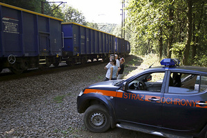 A railway security guards' car is seen next to people observing a cargo train travelling in an area where a Nazi train is believed to be at, in Walbrzych, southwestern Poland August 30, 2015. Poland said on Friday it was almost certain it had located the Nazi train rumored to have gone missing near the close of World War Two loaded with guns and jewels. Polish authorities started looking for the train this month, tipped off by a German and a Pole who said through lawyers that they had found it in the southwestern district of Walbrzych and expected 10 percent of the value of the findings as a reward. REUTERS/Kacper Pempel - RTX1QB42