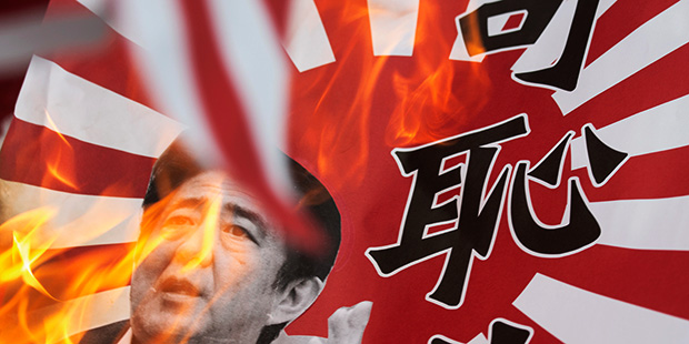 """A rising sun flag with an image of Japanese Prime Minister Shinzo Abe and Chinese characters which reads """"shame"""" is burnt during an anti-Japan protest outside the Japanese Consulate in Hong Kong September 15, 2013. The United States hopes that tentative diplomatic engagement between China and Japan amid their dispute over a group of islands in the East China Sea is successful as escalation is in nobody's interest, a senior U.S. diplomat said on Saturday. Wednesday marks the 82nd anniversary of Japan's invasion of mainland China. REUTERS/Tyrone Siu (CHINA - Tags: POLITICS CIVIL UNREST) - RTX13LVZ"""