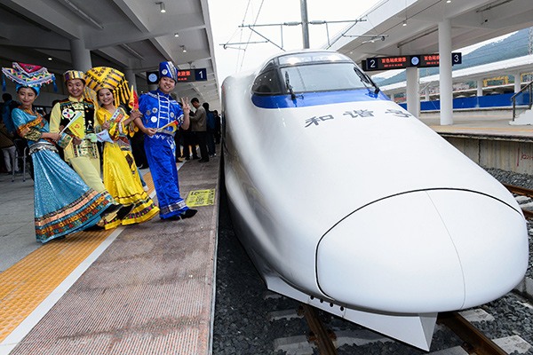 Dec. 11, 2015 (Xinhua) -- People in costumes of different ethnic groups pose for photos beside a high-speed train ready for operaton at the railway station in Bose County, south China's Guangxi Zhuang Autonomous Region on Dec. 11, 2015. The Nanning-Bose section of the passenger railway connecting Nanning , capital of Guangxi, and Kunming, capital of the neighbouring Yunnan Province, was open to operation on Friday. The section is 223 kilometers long with the operation speed of 200 kilometers per hour.