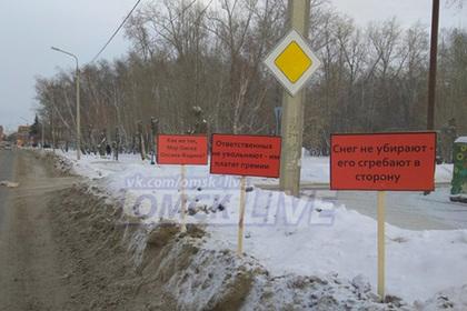 Омичи с помощью табличек призвали власти убрать снег