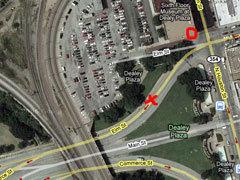 Место, где находилась машина Кеннеди в момент первого выстрела, обозначено крестиком. Место, где находился снайпер, обведено кружком. Фрагмент спутникового снимка Google Maps. Кликните на картинке, чтобы увидеть ее же, но большего размера.
