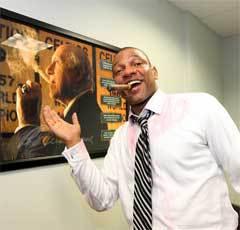 """Док Риверс на фоне плаката с изображением легендарного тренера """"Селтикс"""" Реда Ауэрбаха. Фото с официального сайта НБА"""