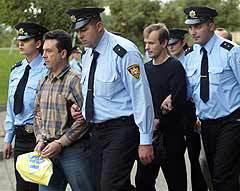 Обвиненные в шпионаже российские военнослужащие в сопровождении грузинской полиции. Фото (c)AP.