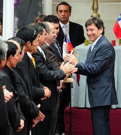 Министр горной промышленности Чили вручает шахтерам памятные подарки. Фото (c)AFP