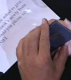 Листок с ответом на вопрос ведущих в руках у Стивена Сигала. Кадр Первого канала