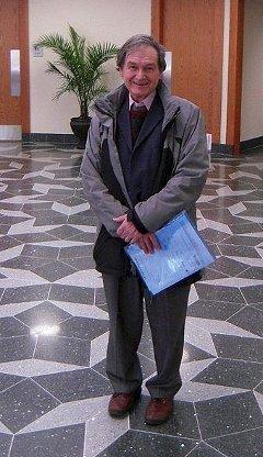 Роджер Пенроуз на полу, выложенном непериодичной мозаикой его изобретения, в фойе Техасского университета. Фото Wikipedia/Solarflare100