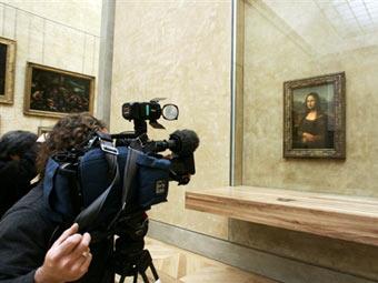 "Съемочная группа перед картиной ""Мона Лиза"" в Лувре. Фото (c)AFP"