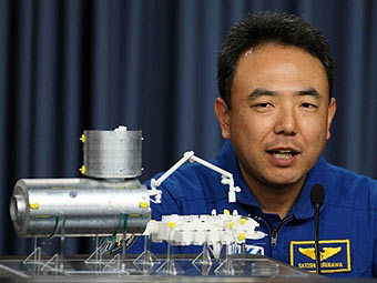 "Японский астронавт Сатоши Фурукава и модель лабораторного комплекса ""Кибо"". Фото AFP"