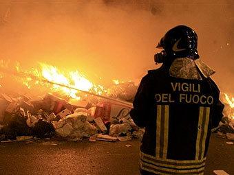 Пожарный тушит горящий мусор на улице Неаполя. Фото AFP