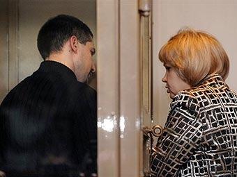 Денис Евсюков общается с адвокатом в зале суда. Фото (c)AFP