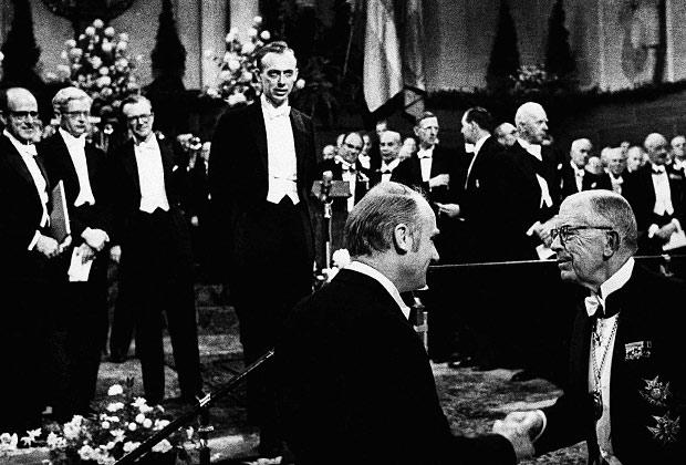 Вручение Нобелевской премии первооткрывателям структуры ДНК. На переднем плане Френсис Крик и король Швеции Густаф Адольф. За награждением наблюдают Макс Перутц, Джон Кендрю, Морис Уилкинс и Джеймс Уотсон.