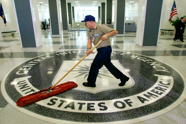 FILE – In this March 3, 2005, file photo a workman quickly slides a dust mop over the floor at the Central Intelligence Agency headquarters in Langley, Va., near Washington. Before Edward Snowden began leaking national security secrets, he twice cleared the hurdle of the federal government's background check system. The first was at the CIA, and the second was as a contract technician at the National Security Agency. (AP Photo/J. Scott Applewhite, File)