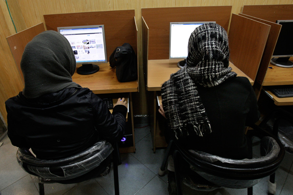 FILE- In this Monday, Feb. 13, 2012 file photo, Iranian women use computers at an Internet cafe in central Tehran. Iran's cyber monitors often tout their efforts to fight the West's 'soft war' of influence through the web, but trying to ban Google's popular Gmail may have gone too far with complaints coming even from email-starved parliament members. (AP Photo/Vahid Salemi, File)