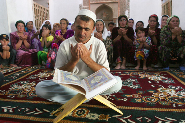 """The keeper of the Mausoleum of Muhammad Bashoro reads the Koran for his followers in the city of Panjakent, 270 km (168 miles) northwest of the Tajik capital Dushanbe, August 12, 2009. The mausoleum, built in the 11th century, is famous for its """"forty-days room"""", where holy men can isolate themselves for 40 days to read and meditate to the Koran. Picture taken August 12, 2009. REUTERS/Nazim Kalandarov"""