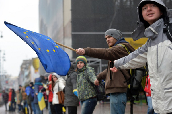 """Ukrainian students stand hand in hand to create a human chain symbolizing the unity of Ukraine with EU during their action in Kiev on November 2013. The chain begins on the Kiev's Independence Square and, according to the organizers, must end at the border with Poland, the nearest EU country bordering the Ukraine. Ukrainian President Viktor Yanukovych told an EU summit on Friday that Kiev wanted to sign a historic pact with the bloc """"in the near future"""" but needed economic and financial aid. The European Union will not accept a Russia """"veto"""" or any other meddling in its ties with other nations, European Commission president Jose Manuel Barroso said Friday"""