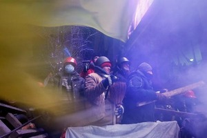 Pro-European Union activists guard the barricade during clashes with riot police in Independence Square in Kiev, Ukraine, Wednesday, Dec. 11, 2013. Security forces clashed with protesters as they began tearing down opposition barricades and tents set up in the center of the Ukrainian capital early Wednesday, in an escalation of the weeks-long standoff threatening the leadership of President Viktor Yanukovych. (AP Photo/Efrem Lukatsky)