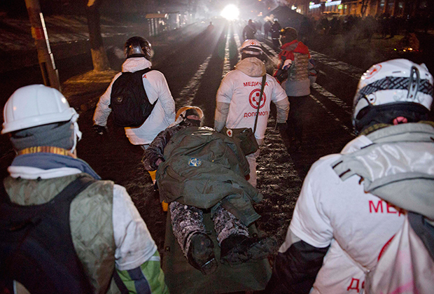 Медики транспортируют раненого демонстранта