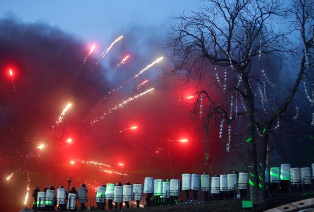 Бойцы «Беркута» защищаются от фейерверков, запущенных активистами оппозиции