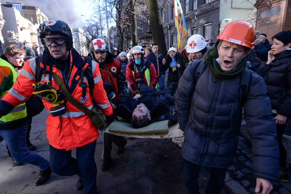An Interior Ministry member, who was injured during clashes with anti-government protesters, is transported on a stretcher in Kiev February 18, 2014. Several thousand anti-government protesters clashed with police near Ukraine's parliament on Tuesday, torching vehicles and hurling stones in the worst violence to rock the capital Kiev in more than three weeks. REUTERS/Andrew Kravchenko/Pool (UKRAINE - Tags: POLITICS CIVIL UNREST)