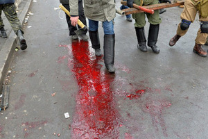 UKRAINE, Kiev : Anti-government protesters walk on a puddle of blood left by a wounded demonstrator during clashes with the police in the center of Kiev on February 20, 2014. Armed protesters stormed police barricades in Kiev on Thursday in renewed violence that killed at least 26 people and shattered an hours-old truce as EU envoys held crisis talks with Ukraine's embattled president. Bodies of anti-government demonstrators lay amid smouldering debris after masked protesters hurling Molotov cocktails and stones forced police from Kiev's iconic Independence Square -- the epicentre of the ex-Soviet country's three-month-old crisis.