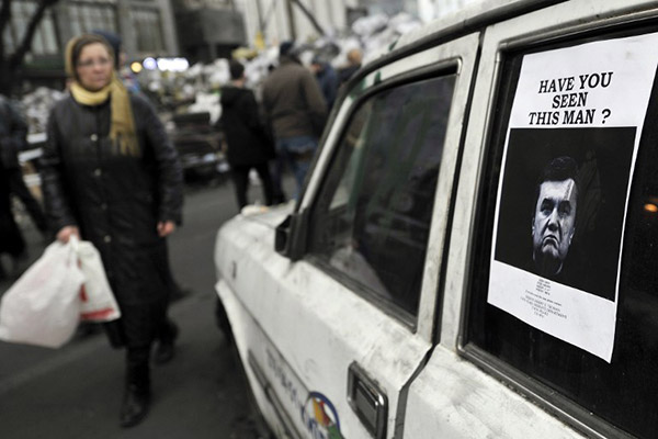 "Ukrainians look at a ""Wanted"" notice for fugitive Ukrainian President Victor Yanukovich, plastered on the window of a car used as barricade near Kiev's Independent Square February 24, 2014. Ukrainian President Viktor Yanukovich, ousted after bloody street protests in which demonstrators were shot by police snipers, is wanted for mass murder, authorities announced on Monday. REUTERS/Yannis Behrakis"