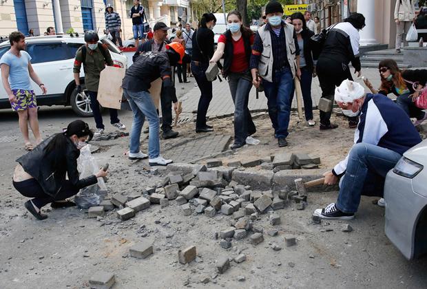 Люди готовят булыжники в качестве боеприпасов во время столкновений 2 мая 2014 года в Одессе