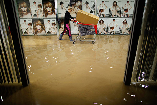 A woman pushes a trolley as she evacuates a hair salon in a shopping centre during flooding in the central Bosnian town of Zenica May 15, 2014. Several Bosnian cities have been affected by floods caused by heavy rains