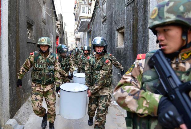 Полицейские несут изъятые во время обыска наркотики (около трех тонн), провинция Гуандун, 29 декабря 2013 года
