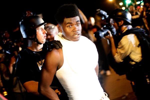 A police officer in riot gear detains a demonstrator protesting against the shooting of Michael Brown, in Ferguson, Missouri August 19, 2014. Police in riot gear ordered dozens of lingering demonstrators in Ferguson, Missouri, to disperse late on Tuesday and charged into the crowd to make arrests as relative calm dissolved amid protests over the police shooting death of Brown, an 18-year-old unarmed black teen, in the St. Louis suburb.