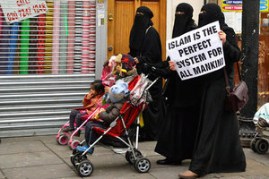 Women hold placards during a march and rally in east London December 13, 2013. They were participating in a rally organised by British Islamist Anjem Choudary condemning use of alcohol and promoting Shariah law.