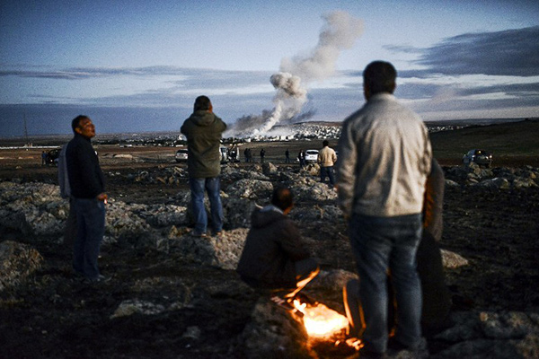 Kurdish people observe smoke rising from the Syrian town of Kobane, also known as Ain al-Arab, following an explosion as seen from the southeastern Turkish village of Mursitpinar in the Sanliurfa province on October 20, 2014. US President Barack Obama called his Turkish counterpart Recep Tayyip Erdogan and they pledged to step up the fight against the Islamic State group in Syria, the White House said. Kurdish fighters have been under IS assault for more than a month around Kobane, which has become a key prize as it is being fought under the gaze of the world's press massed just over the border in Turkey.