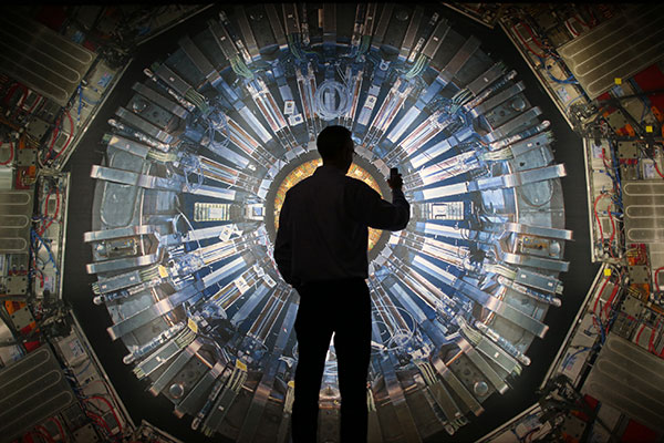 LONDON, ENGLAND - NOVEMBER 12:  A visitor takes a phone photograph of a large back lit image of the Large Hadron Collider (LHC) at the  Science Museum's 'Collider' exhibition on November 12, 2013 in London, England. At the exhibition, which opens to the public on November 13, 2013  visitors will see a theatre, video and sound art installation and artefacts from the LHC, providing a behind-the-scenes look at the CERN particle physics laboratory in Geneva. It touches on the discovery of the Higgs boson, or 'God particle', the realisation of scientist Peter Higgs' theory.  (Photo by Peter Macdiarmid/Getty Images)